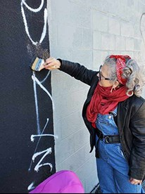 Councilor Crista Patrick painting over graffiti on a wall