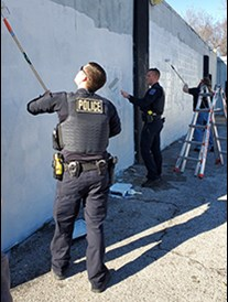 two Tulsa police officers using paint rollers to paint over a wall with graffiti